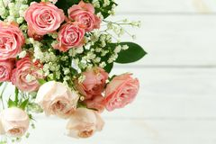 Flowers background. Bouquet of beautiful pink roses. On white wooden background.Top view.Copy space. Holiday background royalty free stock images