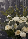Flowers on a background of the urban landscape. White rose in a beautiful bouquet Royalty Free Stock Photo
