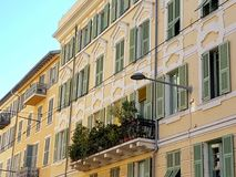 Flowers at a balcony in old Nice, France. A beautiful balcony filled with plants located on an old Yellow house in old Nice Royalty Free Stock Image