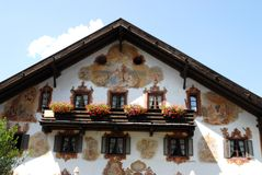 Flowers on the balcony windows and frescoes in Oberammergau in Germany Royalty Free Stock Photo