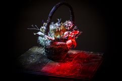Basket with flowers. Dark background royalty free stock photo