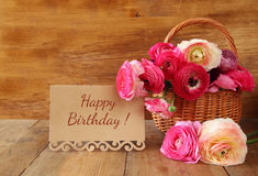 Flowers in the basket next to card with phrase: happy birthday Stock Photos