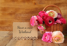 Flowers in the basket next to card, on wooden table Stock Image