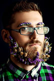 Flowers in beard. Handsome young man in spectacles and a beard of flowers. Black background stock photos