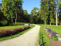 Flowers and beautiful trees, Lithuania. Path colorful flowers and autumn trees in Palanga town park, Lithuania royalty free stock images
