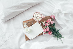 Flowers in bed, good morning concept. Wooden tray with paper sketchbook, marshmallows, candle and spring flowers on clean white bedding. Good morning concept stock photography