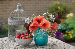 Flowers and berries on the table. Outdoor table decor, in the garden stock photo