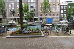 Flowers and bicycles line an Amsterdam canal. A flower box beautifies the sidewalk along an Amsterdam canal lined with bicycles on the sidewalk and boats in the Royalty Free Stock Photography