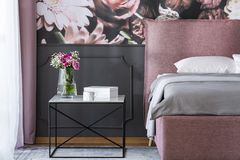 Flowers on black table next to pink and grey bed in bedroom interior with wallpaper. Real photo. Concept royalty free stock images