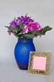 Flowers and blank frame. A blank frame and a blue vase with silk flowers Royalty Free Stock Photos