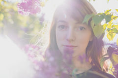 Flowers blooming and Red-haired girl looking at the camera. Royalty Free Stock Photography