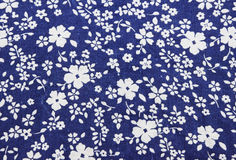 Flowers on blue fabric pattern background Royalty Free Stock Photo