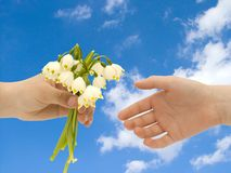 Flowers & blue sky. A little boy giving flowers to a little girl Royalty Free Stock Photography