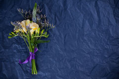 Flowers and blue wrapping paper. Bouquet of yellow and purple flowers and blue wrapping paper. Freesia and wild flowers, floral background Stock Photography