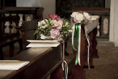 Flowers and booklets on church bench for wedding Stock Photo