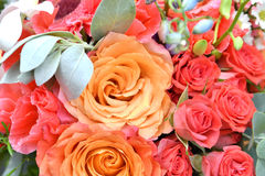 Flowers in bouquet. Close up of orange and pink rose blooms in bouquet with greenery Stock Photo