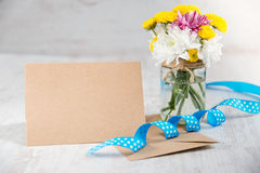 Flowers bouquet in a jar vase with card note, envelope and blue ribbon on a white wood rustic background Royalty Free Stock Photo