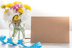 Flowers bouquet in a jar vase with card note, envelope and blue ribbon on a white wood rustic background Stock Images