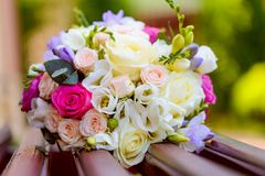 Flowers bouquet laying on bench. One flowers wedding bouquet laying on a wooden bench outside Stock Photos