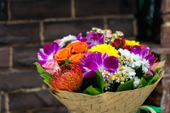 Flowers bouquet with Leucospermum, roses and orchids. In glass vase Stock Image