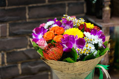 Flowers bouquet with Leucospermum, roses and orchids. In glass vase Stock Photos
