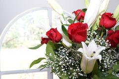 Flowers. Bouquet of roses, lillies, and baby's breath near a window Royalty Free Stock Photos