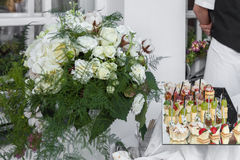 Flowers bouquet and tray canapes Royalty Free Stock Photo