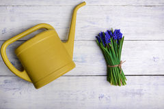 Flowers bouquet with watering can on wooden table. Top view Stock Image