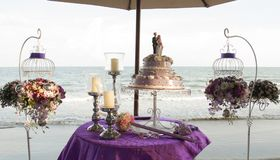 Flowers bouquets and wedding cake on a table on a beach during a traditional Thai wedding stock photo