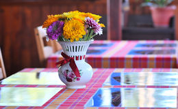 Flowers on a breakfast table. A beautiful bouquet of flowers in a vase on a table Royalty Free Stock Image
