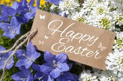 Flowers with brown card board label and happy easter royalty free stock photography