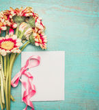 Flowers bunch with blank white greeting card and pink ribbon on shabby chic blue turquoise background Royalty Free Stock Photo