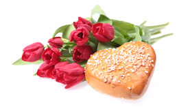 Flowers and cake. Tulips and a heart shaped cake for mothers day Royalty Free Stock Photography