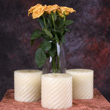 Flowers and Candles. Yellow roses and candles on a table royalty free stock photos