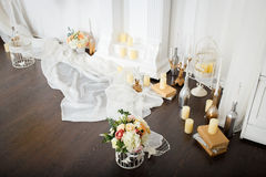 Flowers and candles at the fireplace. Spring flowers decoration beautiful fireplace with candles and unusual wreath on the wall Royalty Free Stock Image