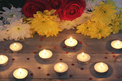 Flowers and candles on a wooden platform stock image