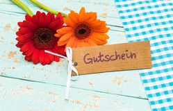 Flowers and card  with german word, Gutschein, means voucher or coupon for Mother`s or Father`s day. Red and orange flowers gift with label with german word Royalty Free Stock Image