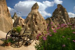 Flowers and carriage in Kapadokya. Flowers with carriage in Kapadokya with stone buildings as background Royalty Free Stock Photography