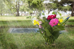 Flowers in Cemetery. Fresh flowers in cemetery with flat headstone, grass and trees in background Stock Photo