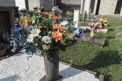 Flowers in cemetery. Fake flowers on a grave in italian cemetery Royalty Free Stock Image