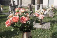 Flowers in cemetery. Fake flowers on a grave in italian cemetery Royalty Free Stock Photos