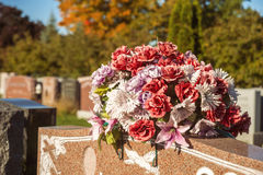 Flowers in a cemetery. With headstones in the background at sunset Stock Photo