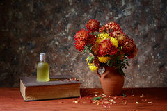 Flowers in a ceramic vase, books and smell in bottle Stock Image