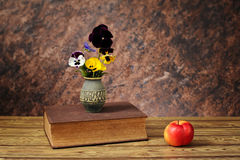 Flowers in a ceramic vase and books Royalty Free Stock Photo