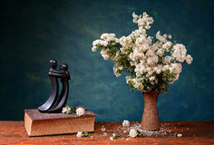 Flowers in a ceramic vase and metal figure Stock Images