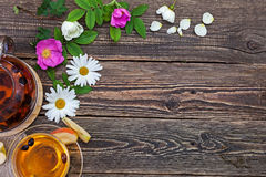 Flowers of chamomile and rose hips on a rough wooden village tab Royalty Free Stock Images