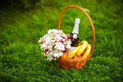 Flowers, champagne and fruit in a basket royalty free stock photography
