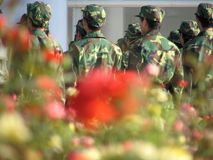 Flowers & Chinese Soldiers. Chinese soldiers doing exercises Royalty Free Stock Images
