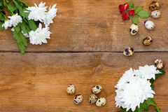 Flowers chrysanthemums, roses and a few quail eggs on old brown wooden background. Stock Image