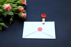 Flowers, clothespins, paper for writing on a dark background. Concept of congratulations on the holiday royalty free stock image